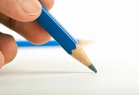 手握铅笔写字的特写图片