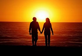 一对中年夫妻手牵手在夕阳下的背影